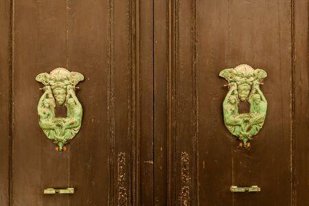 Texture of an old wooden wooden door with unusual metal handles on the island of Malta