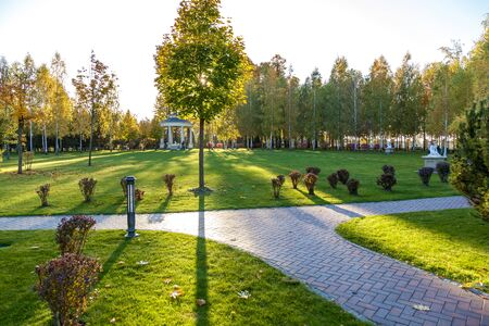 The beautiful park with different plants and cleaned lawns. The stone walkway extends across the lawns. On the background located a small gazebo. Stock fotó
