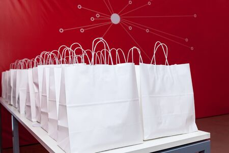 White paper bags on the white table on the red wall background. Bags are placed in two equal rows.