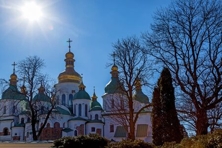 The Saint Sophia Cathedral is surrounded by bare trees against the blue pure sky on a sunny day in Kiev.