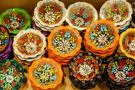 Handmade ceramic bowls are painted in bright colors with floral ornament. The beautiful view on colorful bowls from above. Banco de Imagens