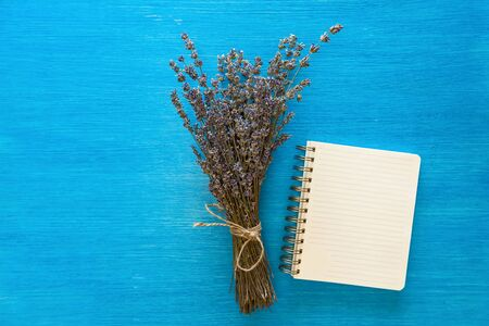 The bunch of violet flowers lying near a notebook on the blue background.