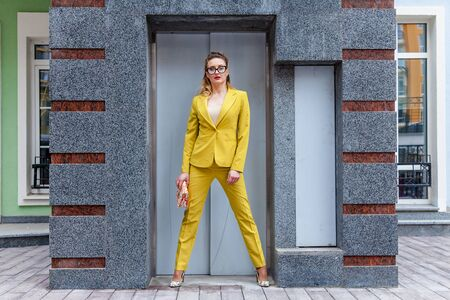 The full-size photo of a business lady in a colorful pantsuit with a pink bag. The model is posing for a photographer near the elevator entrance.