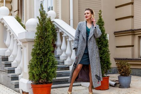 An elegant woman is standing in front of the stairs and talking on the phone. The model wearing a green suit and grey coat on the high heels.