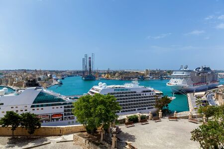 A beautiful panorama of a sea with luxury modern cruise liners near a shore of Malta on the background of a pure blue sky.