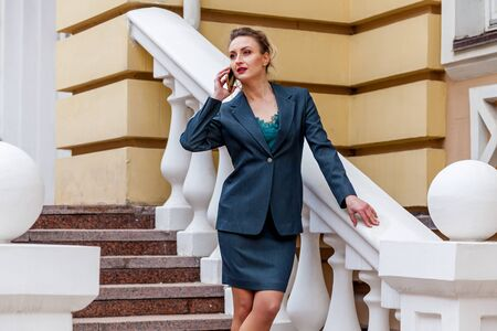 A middle-aged woman in a green suit is standing on the stairs and telling on the phone. Reklamní fotografie