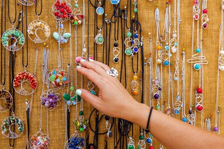 A woman is choosing colorful necklaces at the tourist market in Malta. Close-up view of women s hands with a gem ring.