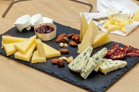 Different types of cheese at a presentation from cheese makers. Top view of a cheese plate with blue cheese, brie with nuts, honey on a wooden table.