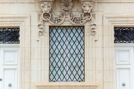 The facade of a historic building with stone decorative elements. An old window with ornamental wrought metal lattice in Malta. Reklamní fotografie