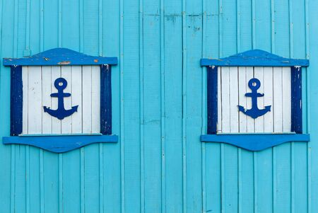 The blue wall of a building with decorative elements such as anchors on the white background.