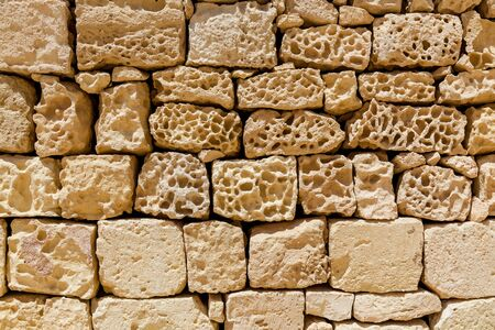 The close-up view of the medieval old stone wall of beige color.