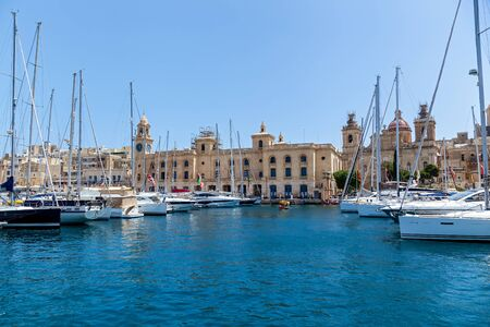 There are a lot of moored yachts in the harbor on the background of Maltese city with old buildings and palm trees on a summer sunny day.