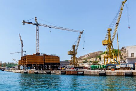 Colorful crane is placed on a floating dock in the harbor, Malta. Seascape with a view of industrial technic.