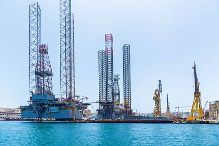 Structures with equipment for drilling oil wells is located in the sea near a shore of Malta on the background of the blue sky.