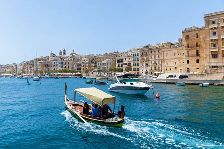 An amazing sea view with traditional Maltese boats on the background of old buildings on a summer sunny day in Malta, Europe. Reklamní fotografie