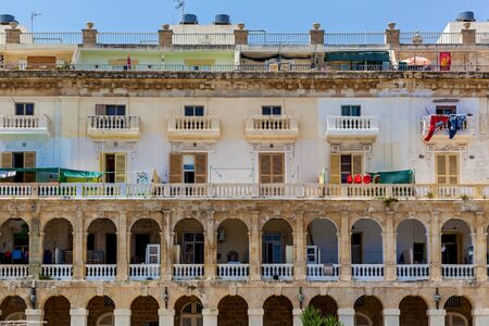 The view of the facade of a residential house with traditional balconies and arches in Valletta, Malta.