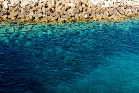 A view of the coast with small stones and with pure blue water. A minimalistic blue texture.