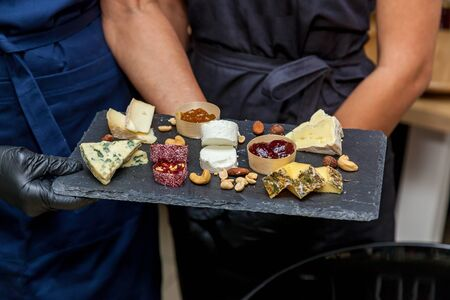 A cheese plate with an assortment of various types of cheese on a dark board on the background of tasters.