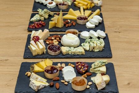 Cheese plates served with jam, nuts, honey at the presentation from cheese makers. Many slices of cheese are placed on presentation boards.