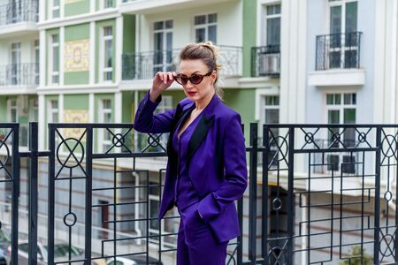 A portrait of a blond woman wearing in a purple suit and glasses poses for a photographer on the balcony of the building with decorative elements.