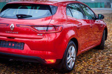 Ucrania Kiev 24 de septiembre de 2019: Un nuevo coche Renault Megane Sedan de color rojo está aparcado en el parque de otoño con muchas hojas caídas.