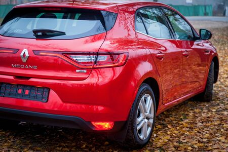 Ukraine Kiev September 24, 2019: A new car Renault Megane Sedan red color is parked in the autumn park with many fallen leaves.