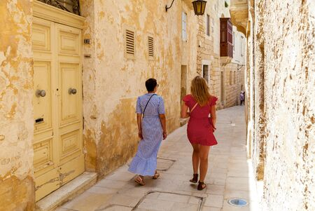 Back view of the women in bright dresses which strolling between the ancient walls of traditional Maltese buildings, Mdina, Malta.