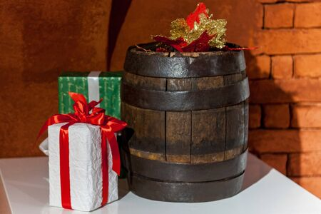 A wooden wine barrel and bright presents on the white table on the background of the brick wall. Reklamní fotografie