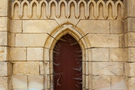 An old brick facade with a wooden church door and figured decorations.