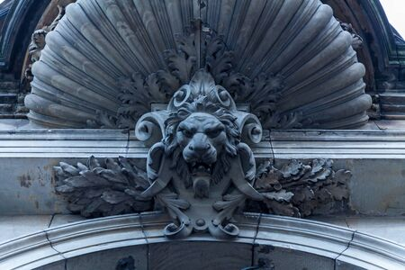 Beautiful stone decorations above the entrance door with the lions head