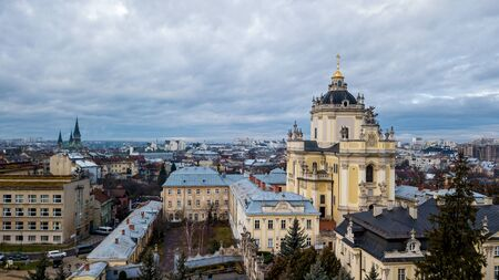 A beautiful view of the church with dark domes and yellow walls in the middle of the center of a city in Lviv. Archcathedral Cathedral of St. George Stock Photo