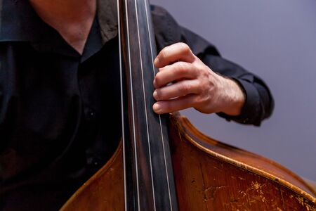 A musician with a double bass in a dark suit playing on the background of a wall.