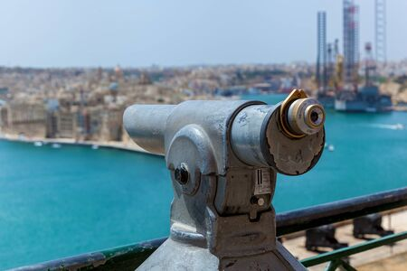 The old monocular for tourists points out to the seashore on a sunny day. Amazing landscape of the coastal city in Malta.