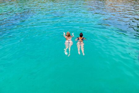 Two women in dark swimsuits are swimming in the pure turquoise water of the sea on a sunny day.