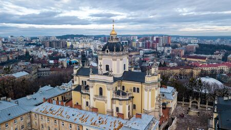 A beautiful view of the church with dark domes and yellow walls in the middle of the center of a city in Lviv. Archcathedral Cathedral of St. George Фото со стока