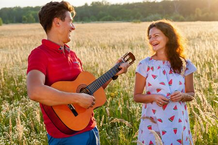 A young man with the guitar is standing near his pregnant wife in the wheat field on a sunny day.Pregnant family photo shoot in nature Banque d'images