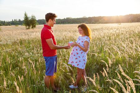 A beautiful outdoor image of a young man giving a present to his pregnant wife.Pregnant family photo shoot in nature