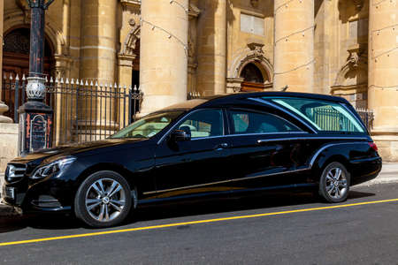 Malta Valletta June 16, 2019: A luxury car parked near the facade of traditional Maltese building on a summer day.