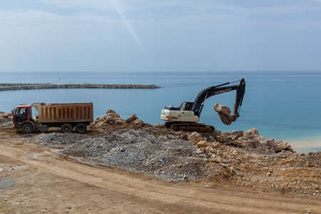 Turkey Alanya April 18, 2018: An old excavator is working on the seashore to prepare it for tourists. A big truck is standing near an excavator and waiting to load the stones.