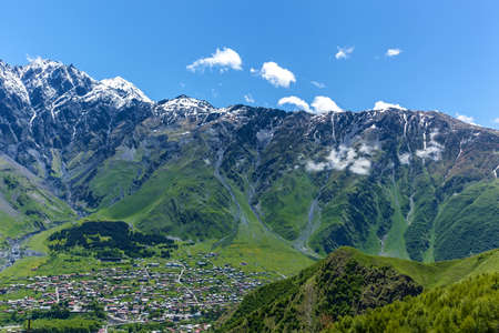 The village of Stepantsminda in the Kazbegi reserve is surrounded by beautiful high mountains with snow caps on the tops. Mtskheta-Mtianeti region in Georgia. Kazbegi Village Georgia Фото со стока