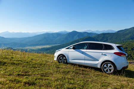 A white car stands on a slope against the backdrop of beautiful green mountains in Adygea