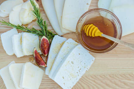 Chopped cheese of different varieties watered with honey, figs and a cup with honey on a wooden board background Reklamní fotografie