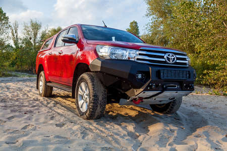 Ukraine Kiev October 10, 2020: Red new 4x4 pickup with Toyota Hilux double cab, with reinforced metal bumper and winch. Japanese car brand.
