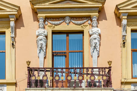 The baroque facade of the building with a balcony and stone sculptures. Sculptures of beautiful goddesses located on the wall.