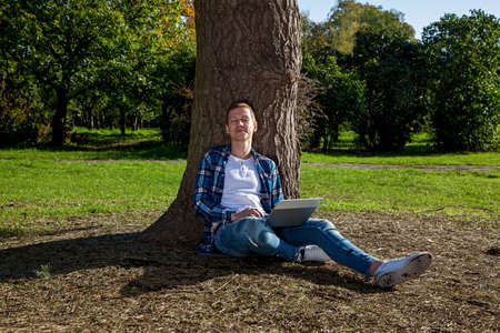 The guy sits near a tree in the park and works on a laptop. Freelance work outdoors. Working outside the office due to the Covid 19 pandemic
