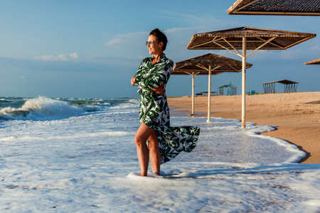 Girl in white dress with green leaves posing on the beach near sun umbrella. Girl in dress posing on the beach 版權商用圖片