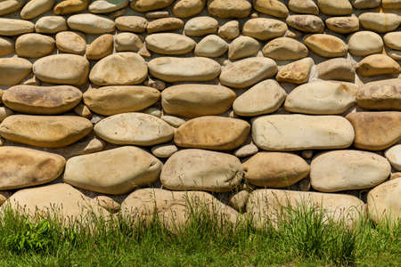 The foundation of the house is decorated with large round white stones. Round stone wall