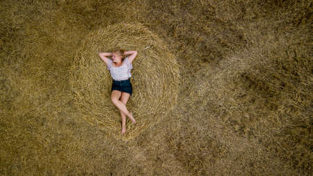 Young girl posing on a round haystack, top view.