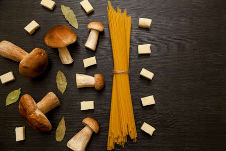 White forest mushrooms on a dark background with spices, spaghetti and pieces of cheese. Fresh mushrooms on a wooden table. 版權商用圖片