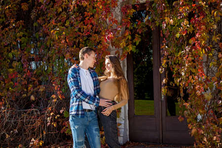 Young beautiful couple in love in a good mood posing against the background of red leaves of wild grapes growing on the house. Young couple in the park